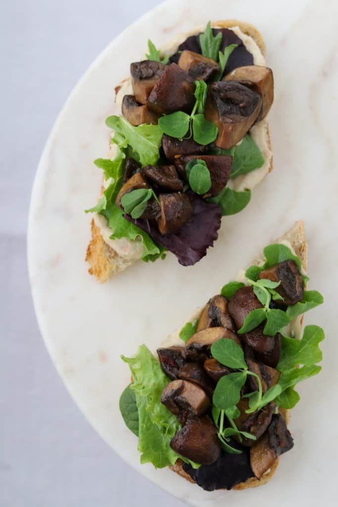Open sandwiches on a plate with lettuce and mushrooms