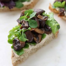 A close up of an open sandwich with mushrooms and lettuce