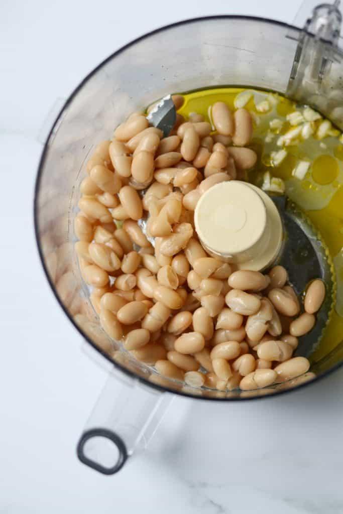 White beans, garlic and olive oil in a food processor work bowl