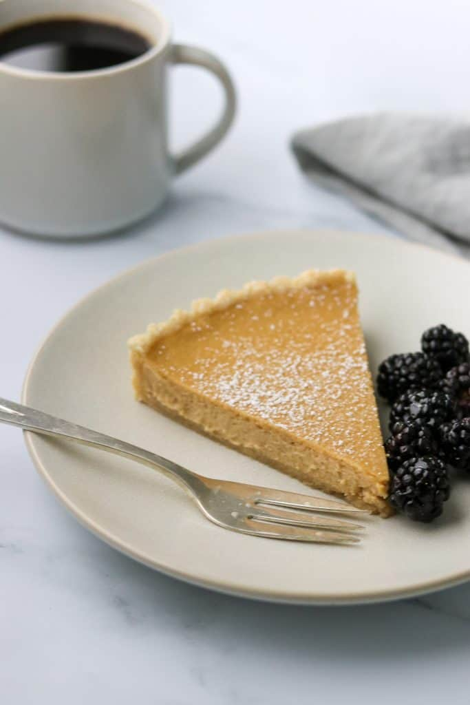 A slice of brown sugar skyr tart on a plate with blackberries and a fork