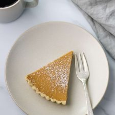A slice of brown sugar skyr tart on a plate with a fork, napkin and a cup of coffee