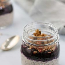 Overnight oats topped with blueberry and granola in a jar with a spoon