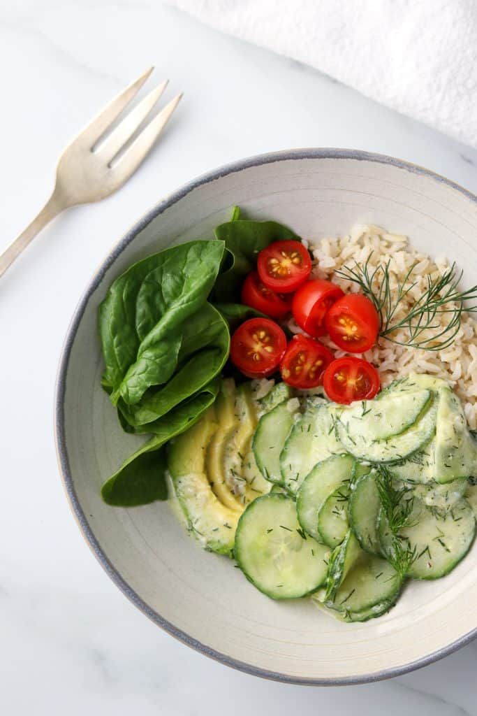 A bowl filled with spinach, avocado, sliced cherry tomatoes, rice and cucumber salad with a fork