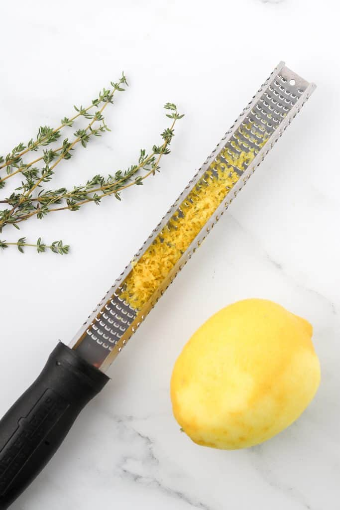 Fresh thyme sprigs, a lemon zester with lemon zest and lemon