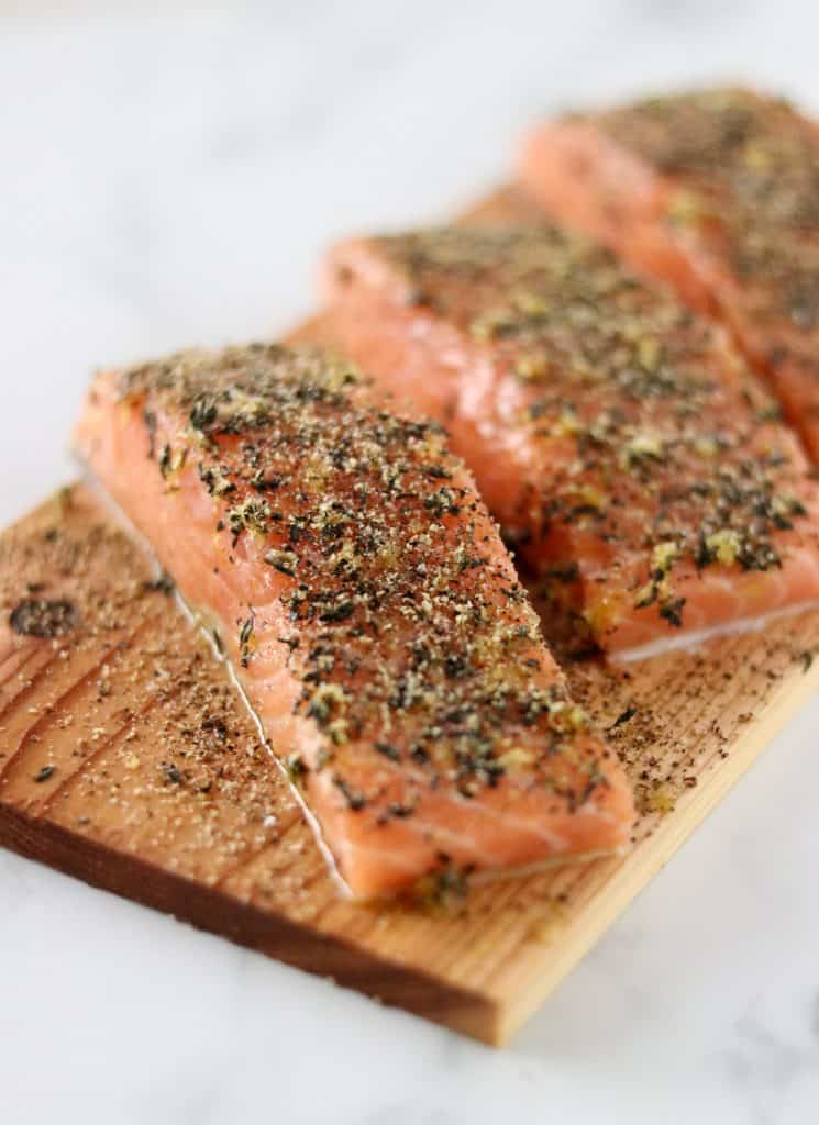A close up of salmon filets on a cedar plank