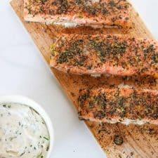 Salmon filets on a cedar plank with a creamy sauce