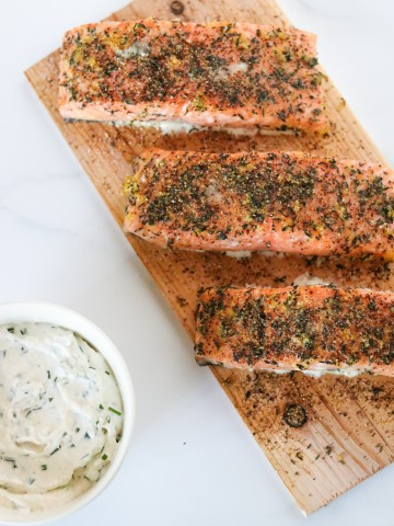 Salmon filets on a cedar plank with a creamy sauce