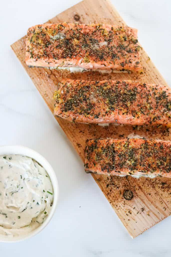 Grilled salmon filets on a cedar plank with a creamy sauce