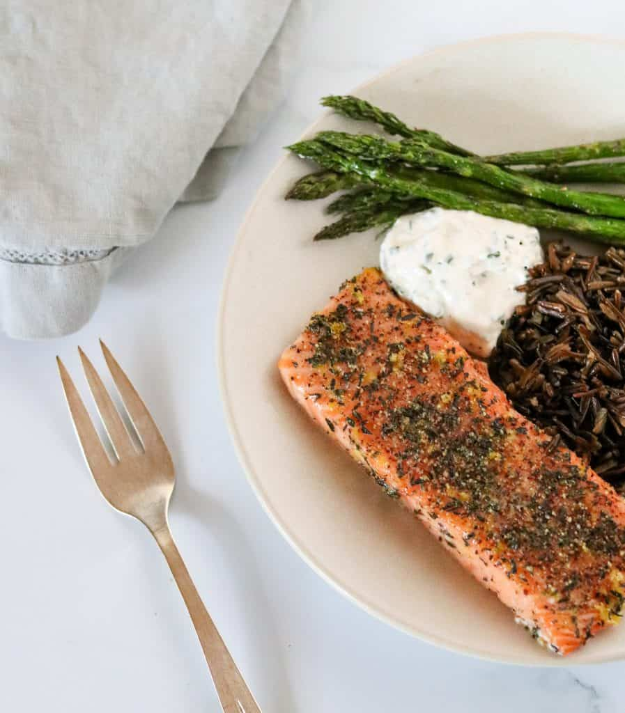 Grilled salmon, asparagus, wild rice and creamy sauce on a plate with a fork and napkin