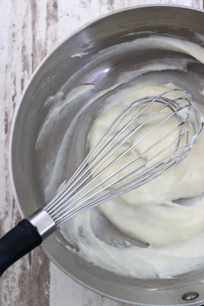Vanilla custard in a saucepan with a whisk