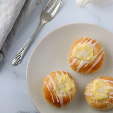 Custard filled buns on a plate with a fork and napkin