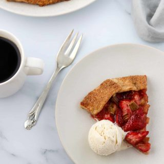 Slice Rustic Strawberry Rhubarb Rye Galette on a plate with ice cream