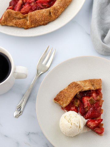 A slice of strawberry rhubarb galette with a scoop of ice cream and a fork and a cup of coffee
