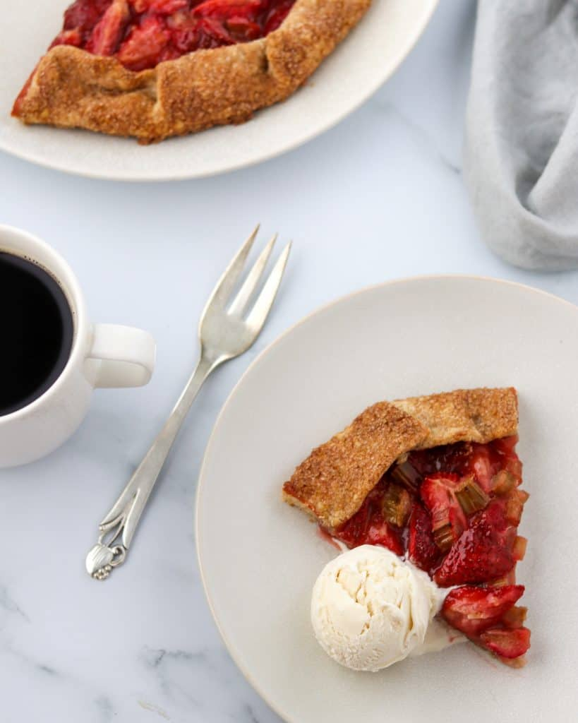 A slice of strawberry rhubarb galette with ice cream and a fork and a cup of coffee