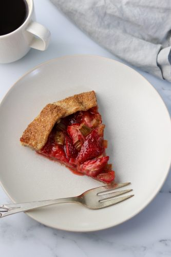Slice of Rustic Strawberry Rhubarb Rye Galette on a plate