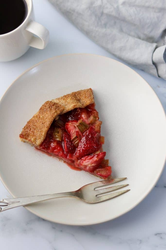 A slice of strawberry rhubarb galette on a plate with a fork