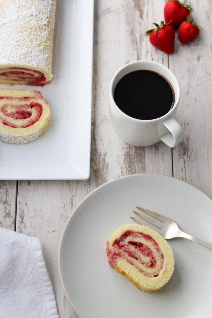 A slice of strawberry rolled cake on a plate with a fork and a cup of coffee