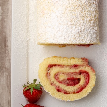 A slice of strawberry rolled cake on a plate with fresh strawberries