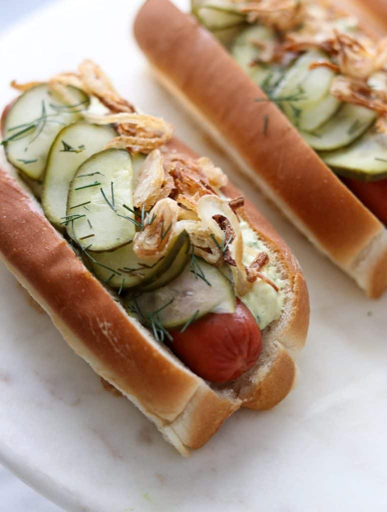 A close up of a hot dog on a bun covered in pickled cucumbers, crispy shallots and creamy sauce