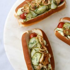 Hot dogs on buns with pickled cucumbers on a plate