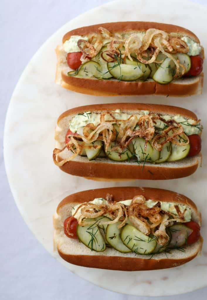 Hot dogs on buns with pickled cucumbers, crispy shallots and creamy sauce on a plate