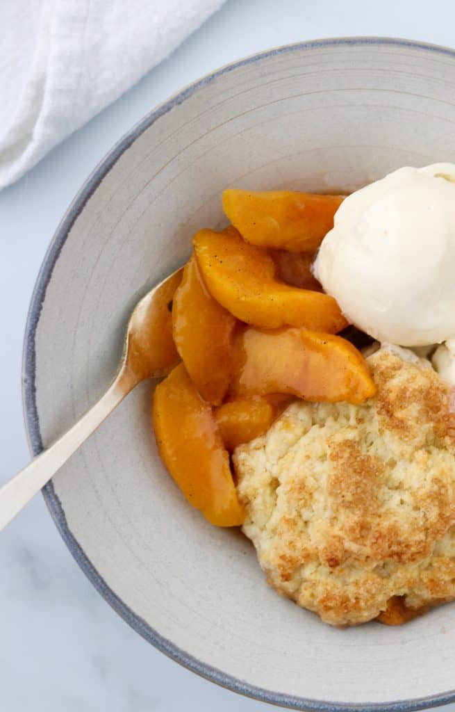A bowl of peach cobbler with ice cream and a fork