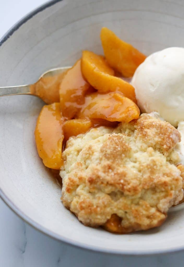 A bowl of peach cobbler and ice cream with a fork