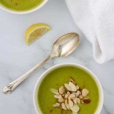 A bowl of zucchini soup topped with sliced almonds and a spoon and lemon wedge