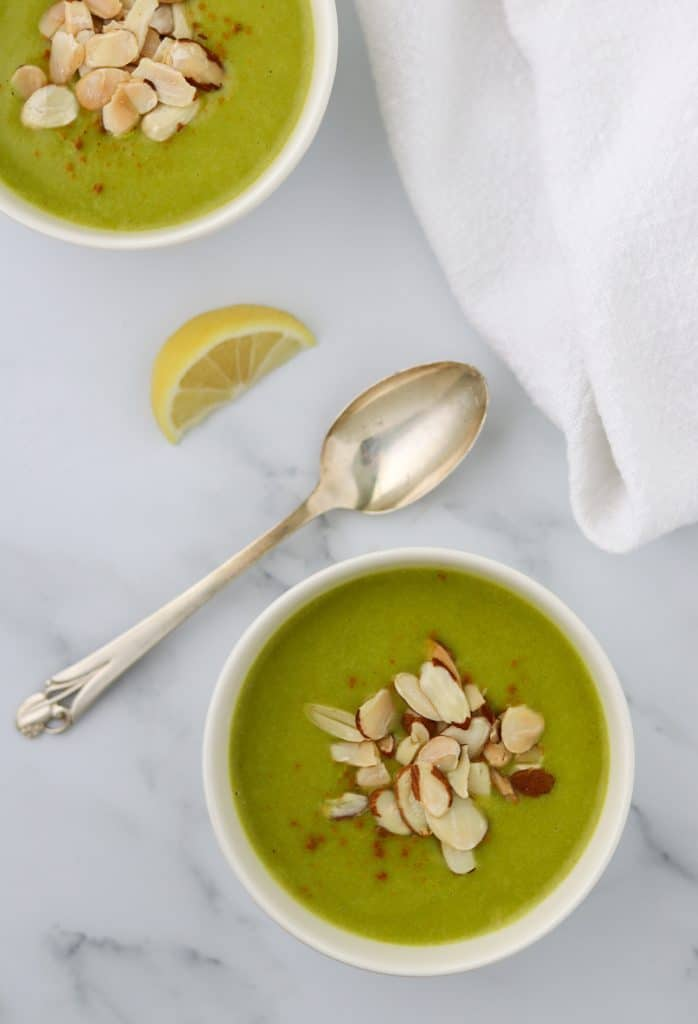 A bowl of zucchini soup topped with almonds and a spoon and lemon wedge