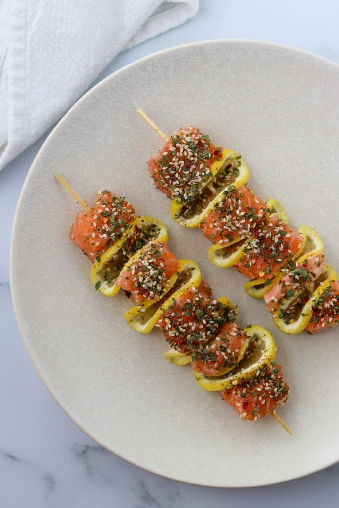A plate with salmon skewers with lemon slices