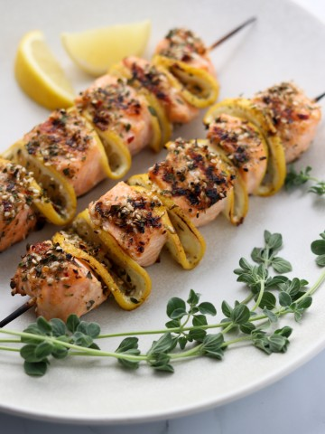Salmon skewers on a plate with lemon and fresh herbs