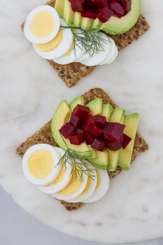 Toast topped with sliced egg, avocado and pickled beets on a plate