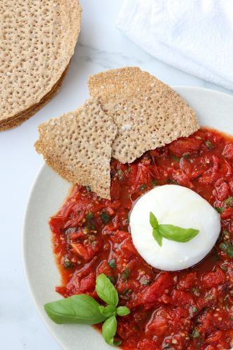 A plate with tomatoes, basil, burrata and crispbread