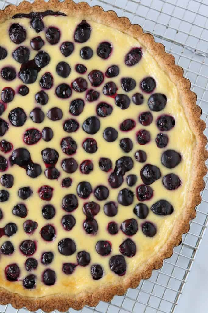 A close up of a blueberry tart on a cooling rack