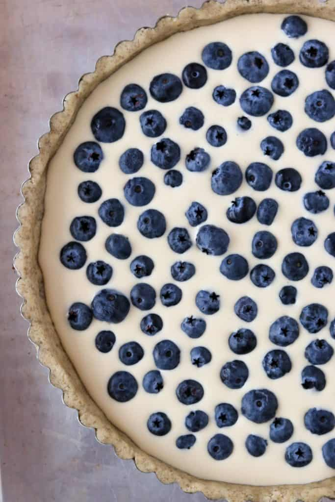 A close up of an unbaked blueberry tart