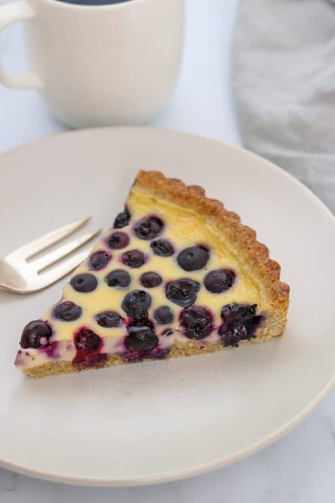 A close up of a slice of blueberry tart on a plate with a fork