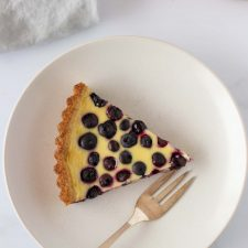 A slice of blueberry tart on a plate with a napkin and fork