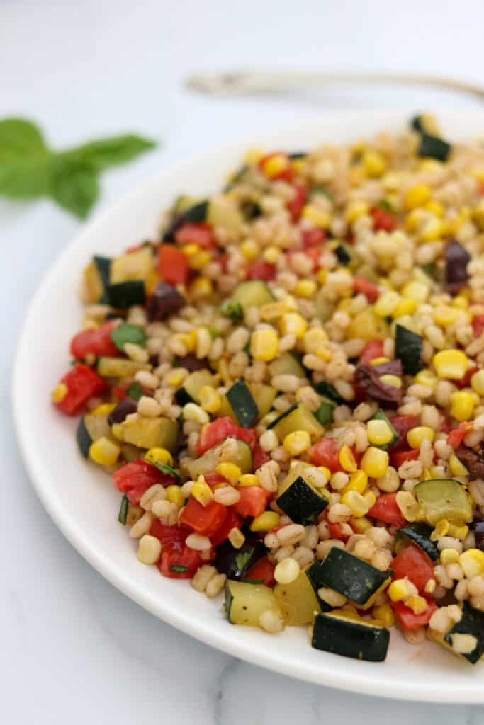 A plate of barley salad with corn, zucchini and tomatoes