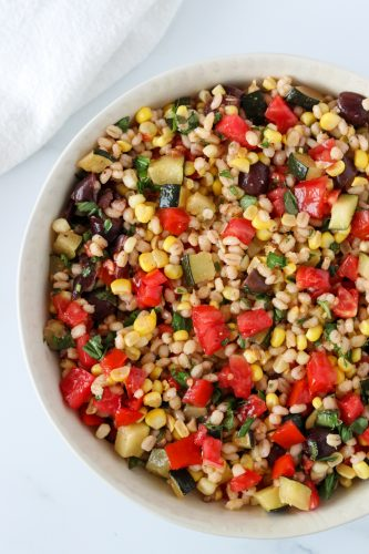 A bowl of barley salad with corn, zucchini and tomatoes