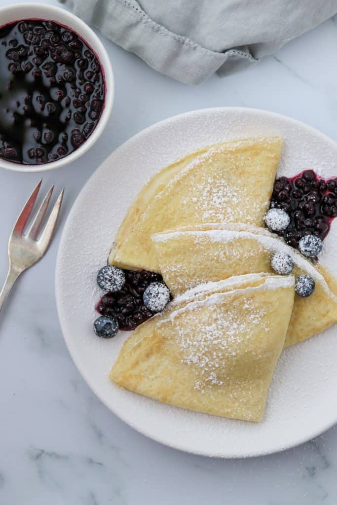 A plate of Swedish pancakes with blueberries and a fork
