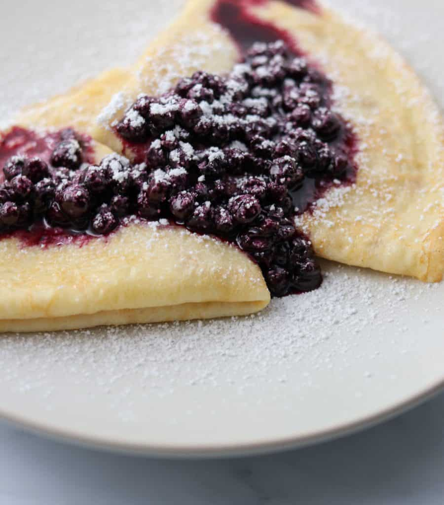 Swedish pancakes on a plate with blueberry compote