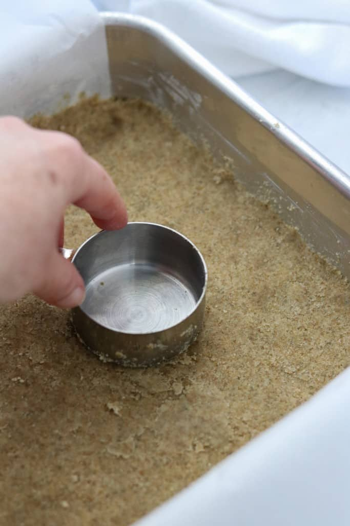Person smoothing unbaked crust with the back of a measuring cup