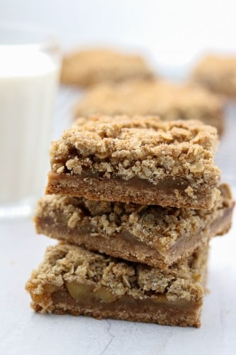 A close up of a stack of apple crumble bars with a glass of milk