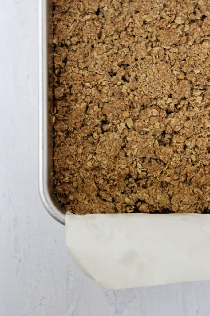 Baked crumble bars in a pan on a wood surface