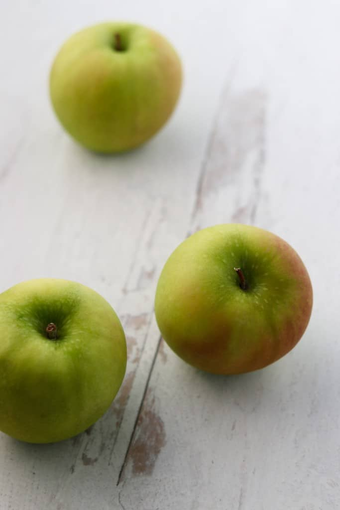 Three green apples on wooden surface