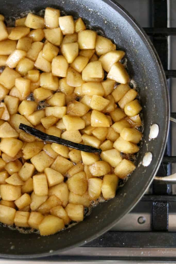 Cubes of apple and a vanilla bean cooking in a skillet