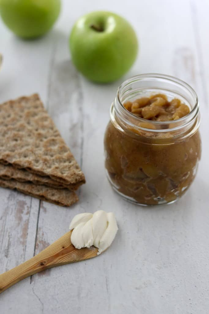 Caramelized apple compote in a jar next to apples, crispbread and a wooden knife with cream cheese