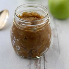 Caramelized apple compote in a jar next to a spoon and apples