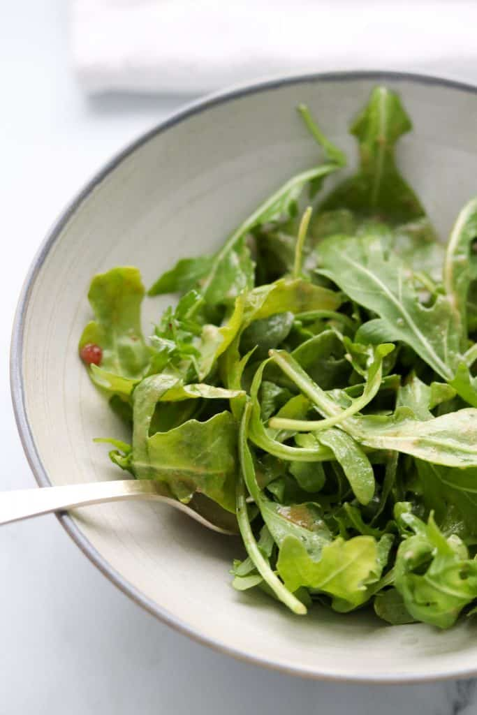 Arugula salad in a bowl with a fork