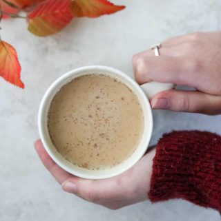 Person holding pumpkin spice latte in a mug with fall leaves